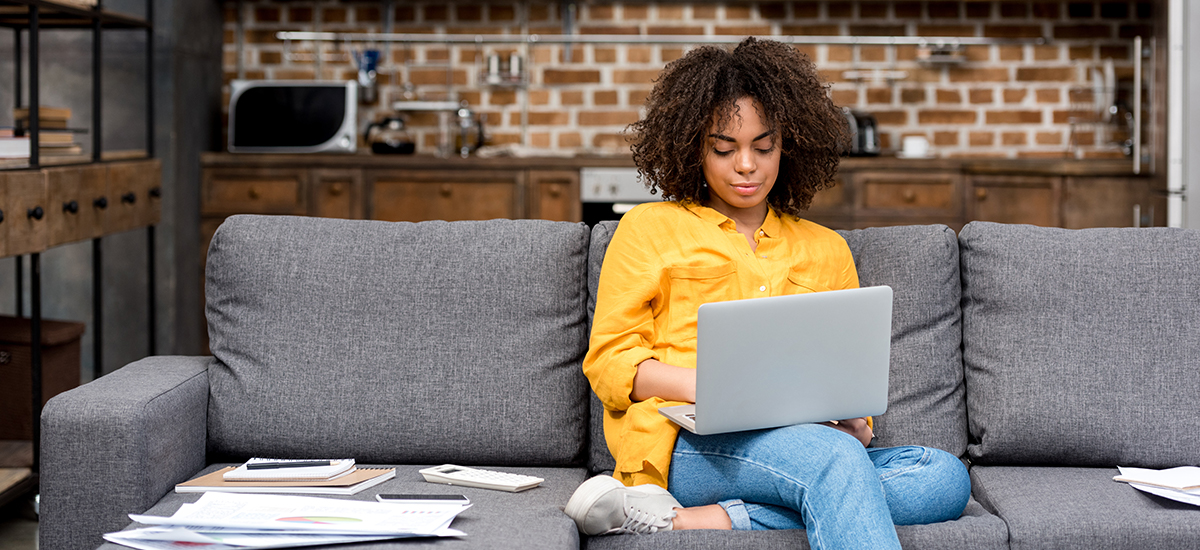 am-image-woman-sits-on-couch-remote-working
