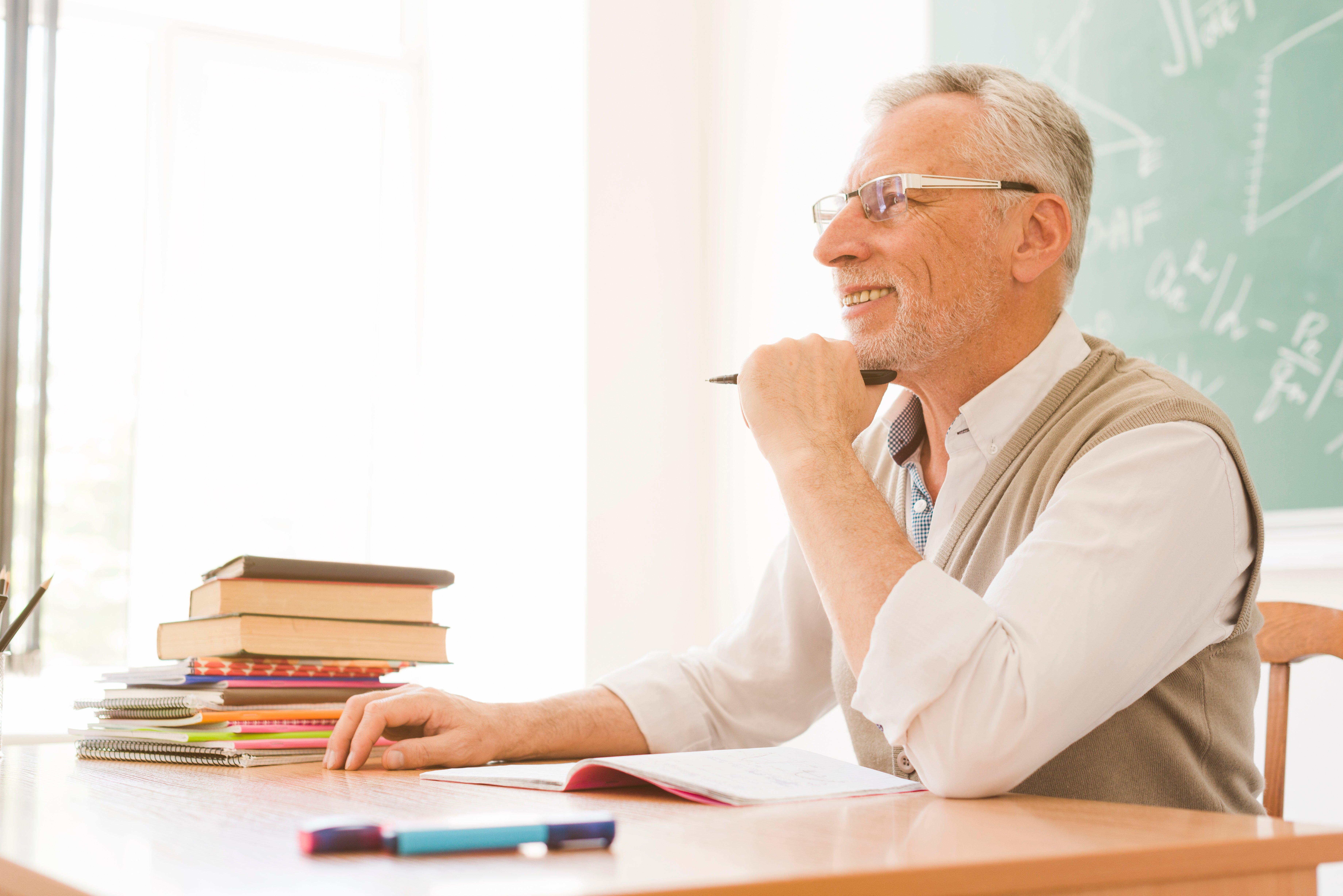 elderly-lecturer-sitting-at-desk-in-auditorium