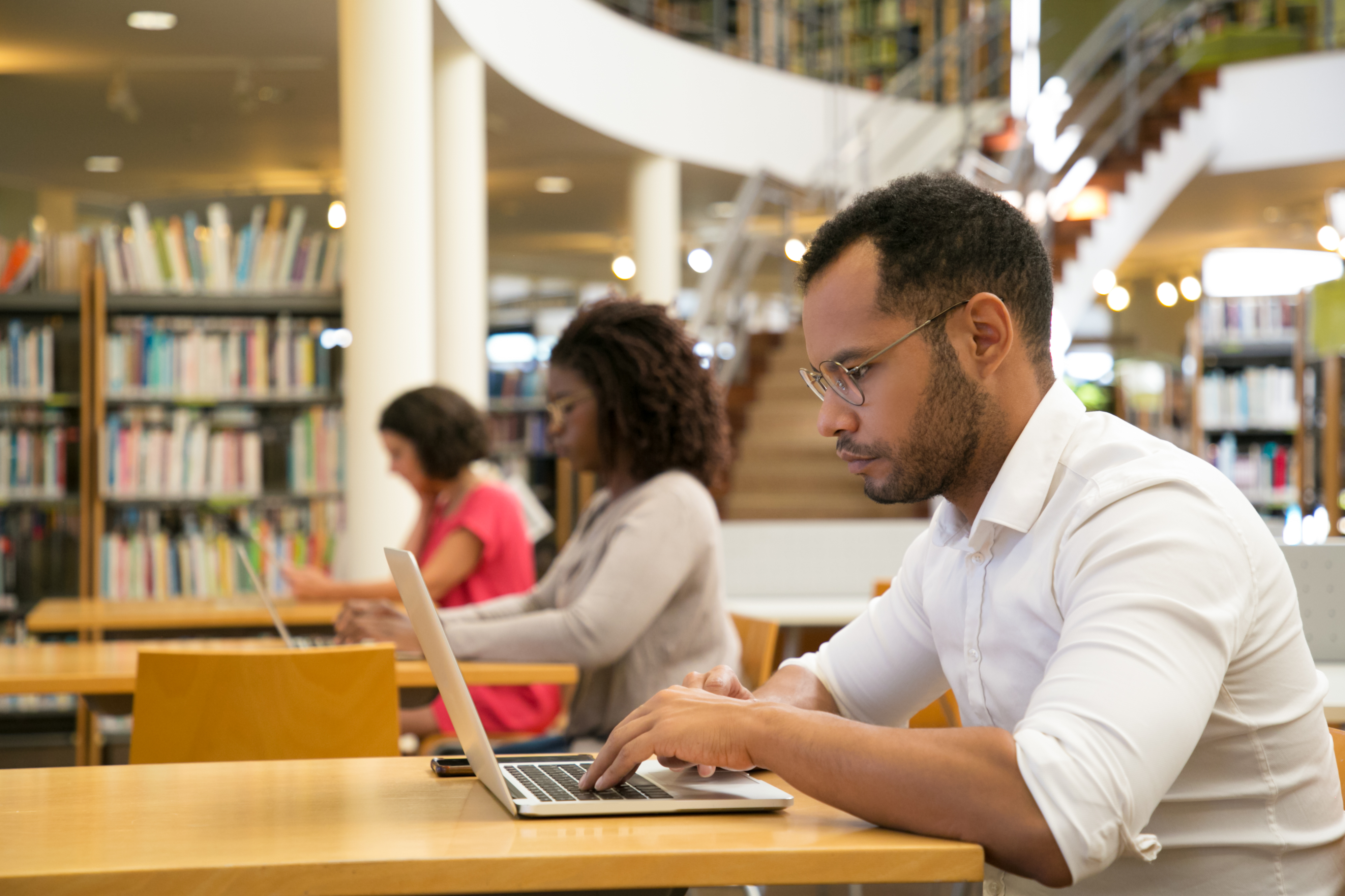mix-raced-trainees-working-on-computer-in-public-library