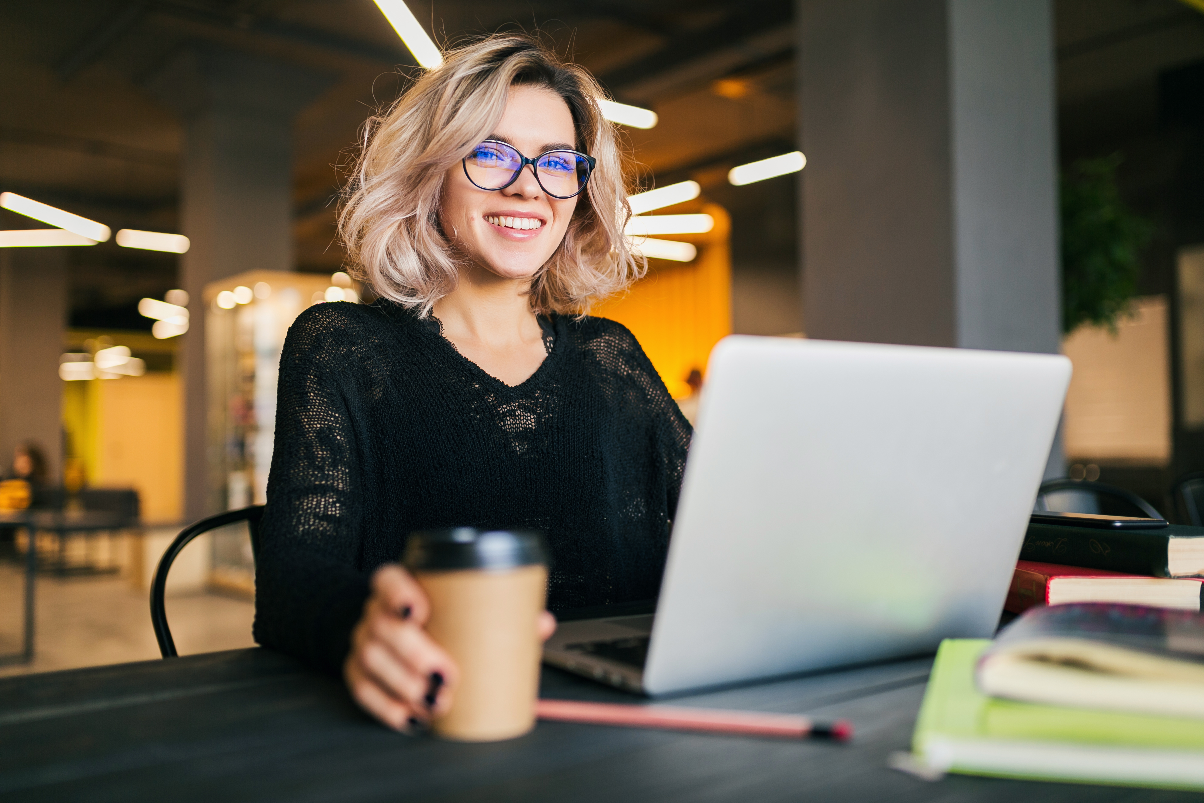 portrait-of-young-pretty-woman-sitting-at-table-in-black-shirt-working-on-laptop-in-co-working-office